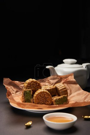selective focus of traditional chinese mooncakes, tea pot and gold ingots on wooden table isolated on black