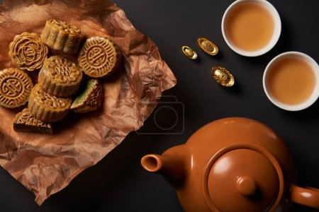 top view of mooncakes, tea pot and gold ingots isolated on black