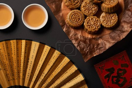 top view of traditional chinese mooncakes with tea and hand fan isolated on black