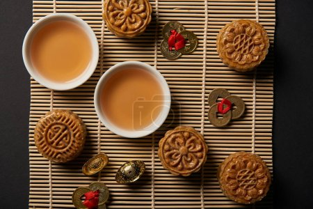 Photo pour Vue du dessus de mooncakes, feng shui coins et théière avec tasses sur tapis de table en bambou - image libre de droit