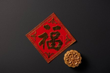 top view of traditional mooncake and chinese hieroglyph isolated on black