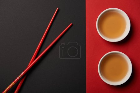top view of chopsticks with traditional chinese tea on red and black background