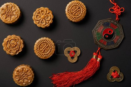 Photo for Top view of traditional mooncakes with chinese talismans isolated on black - Royalty Free Image