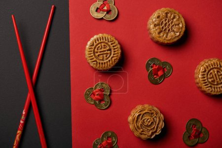 Photo for Top view of mooncakes, feng shui coins and chopsticks on red and black background - Royalty Free Image