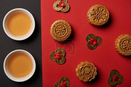 top view of mooncakes, feng shui coins and cups with tea on red and black background