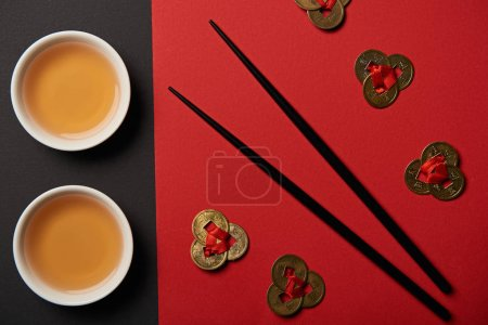 Photo for Top view of tea cups, feng shui coins and chopsticks on red and black background - Royalty Free Image