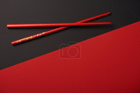 Photo for Top view of chopsticks on red and black background with copy space - Royalty Free Image