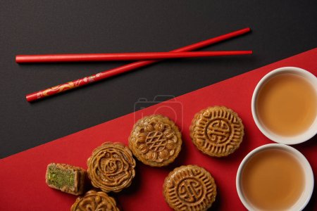 top view of traditional chinese mooncakes with chopsticks on red and black background