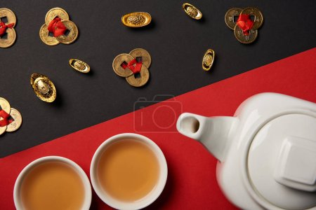 top view of tea pot, cups, gold ingots and feng shui coins on red and black background