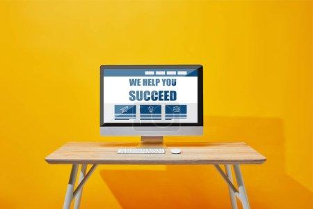 Photo pour Ordinateur avec clavier et souris à la table en bois avec nous vous aidons à réussir le lettrage à l'écran - image libre de droit
