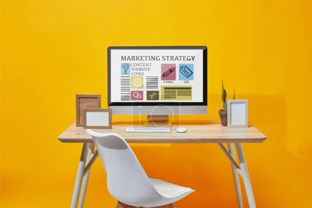 Photo pour Computer with marketing strategy website on screen at wooden table on yellow background - image libre de droit