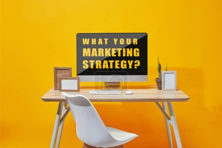 Computer with what your marketing strategy question on screen at wooden table on yellow background