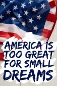united states flag with america is too great for small dreams quote on white wooden surface