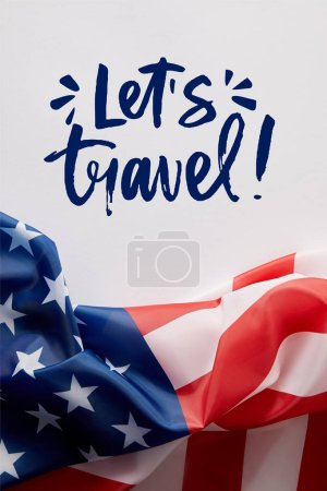 top view of united states of america flag and lets travel lettering on white surface