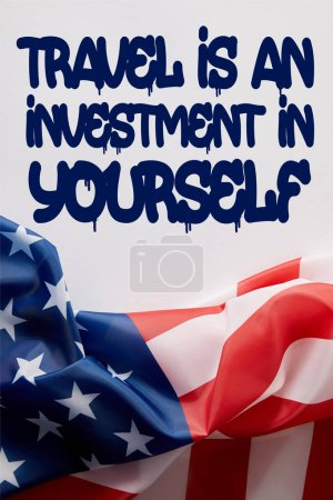 top view of united states of america flag and travel is an investment in yourself quote on white surface