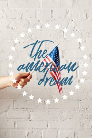 Photo for Cropped image of man holding american flagpole against white brick wall with the american dream illustration - Royalty Free Image