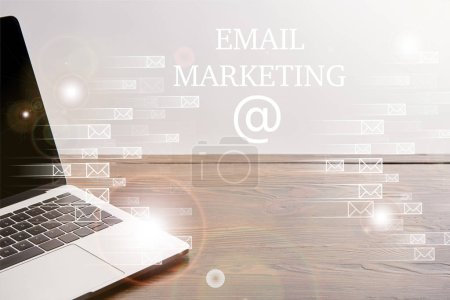 Photo for Close up view of laptop on wooden table with icons and email marketing lettering - Royalty Free Image