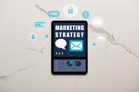 top view of digital tablet with marketing strategy illustration on white marble surface