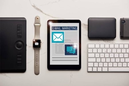 Foto de Flat lay with various wireless devices and email marketing illustration on white marble surface - Imagen libre de derechos