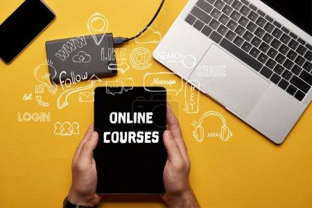Foto de Recorta la vista del hombre que sostiene la tableta digital con ilustración de cursos en línea - Imagen libre de derechos