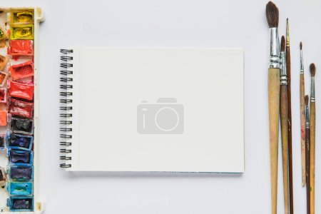 top view of white background with album for drawing, multicolored paints and paintbrushes