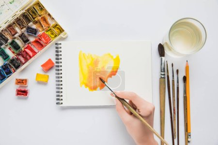 Photo for Top view of female hand drawing in album with watercolor paints and paintbrush - Royalty Free Image