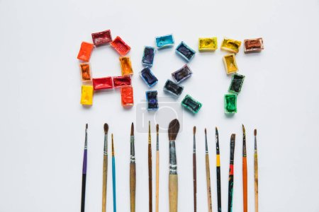 Photo for Top view of paintbrushes and art lettering made of paints on white background - Royalty Free Image