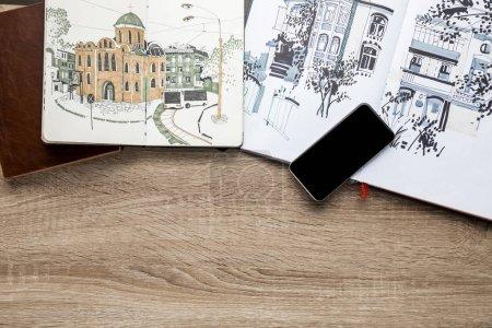 Photo pour Vue de dessus des dessins dans les albums et smartphone sur fond en bois - image libre de droit