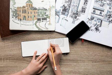 Photo pour Vue du dessus des mains de femmes dessinant sur papier, albums avec peintures et smartphone sur fond en bois - image libre de droit