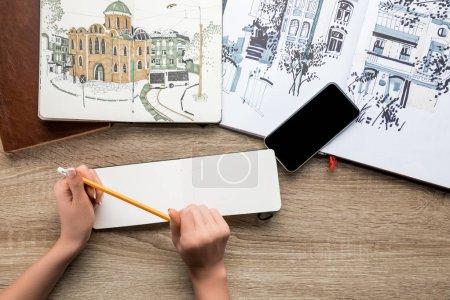 Photo pour Vue de dessus des mains de womans tenir crayon, albums avec les peintures et smartphone sur fond en bois - image libre de droit
