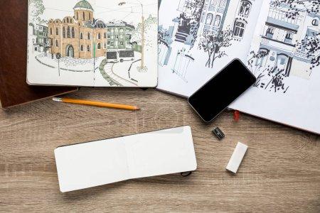 Photo pour Vue de dessus des photos dans des albums, dessin ustensiles et smartphone sur fond en bois - image libre de droit