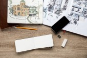 """Постер, картина, фотообои """"вид сверху фотографии в альбомах, рисование посуды и смартфон на деревянных фоне"""""""