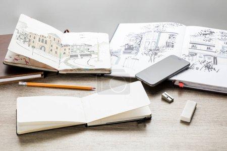 Photo pour Mise au point sélective de l'élaboration des albums, ustensiles et smartphone de dessin sur table en bois - image libre de droit