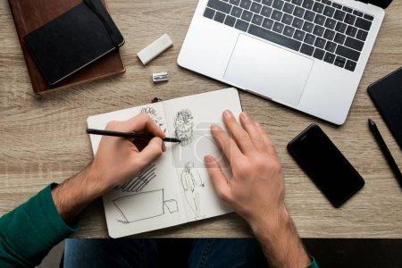 Photo pour Vue du dessus des mains mans dessinant sur l'album et le smartphone à côté de l'ordinateur portable sur la table en bois - image libre de droit