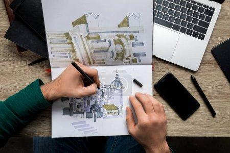 Photo pour Vue du dessus des mains mans dessin dans l'album sur table en bois à côté de l'ordinateur portable et smartphone - image libre de droit