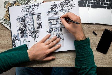 Photo pour Vue du dessus des mains mans dessin dans l'album sur table en bois à côté du smartphone et ordinateur portable - image libre de droit