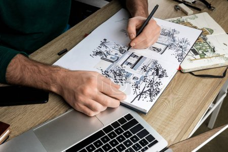 Photo pour Foyer sélectif des mains mans dessin dans l'album sur la table en bois à côté des ustensiles - image libre de droit