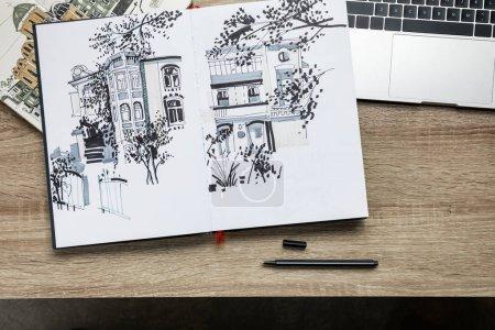 Draufsicht auf Zeichnungen in Alben und Laptops auf Holzgrund