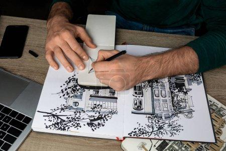 Photo pour Vue de dessus du mans mains dans cahier de dessin sur table en bois à côté des albums et des gadgets - image libre de droit