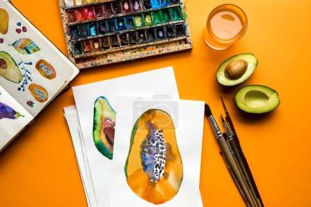 Photo for Top view of colored paints, paintbrushes, sketchbook, drawings with avocado and papaya on yellow background - Royalty Free Image