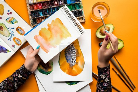 Photo for Top view of female hands drawing avocado and papaya with watercolor paints, paintbrush on yellow table - Royalty Free Image