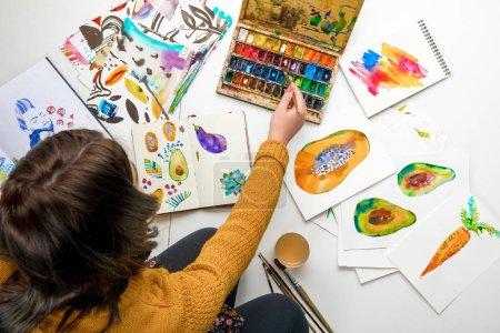 Photo pour Vue de dessus des femmes mélangeant des peintures à l'aquarelle tout en étant entouré de dessins en couleur - image libre de droit