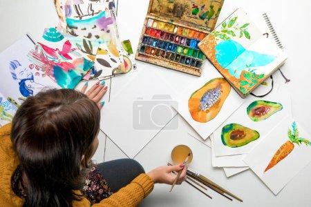Photo pour Vue de dessus de femme prépare à peindre à l'aquarelle peint entouré de dessins en couleur et dessin ustensiles - image libre de droit
