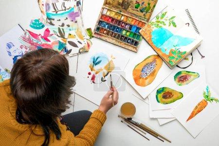 Photo pour Vue de dessus de femme peinture à l'aquarelle peint entouré de dessins en couleur et dessin ustensiles - image libre de droit