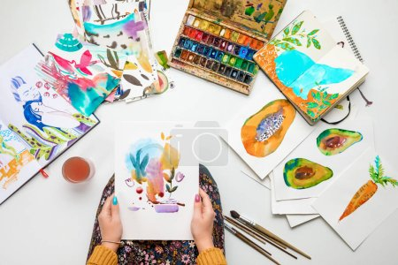 top view of woman holding watercolor drawing while surrounded by color pictures