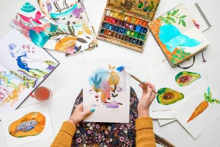 Photo pour Vue de dessus de femme tenant le dessin sur les genoux et la peinture dedans avec les peintures aquarelles entouré de photos couleurs - image libre de droit