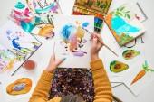 """Постер, картина, фотообои """"вид сверху женщина, держащая опираясь на колени и живопись в нем с Акварель краски в окружении цветные картинки"""""""