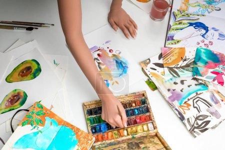 Photo pour Foyer sélectif des mains féminines mélangeant des peintures à l'aquarelle entourées d'images couleur - image libre de droit