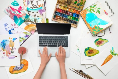 top view of female hands on laptop while surrounded by watercolor drawings