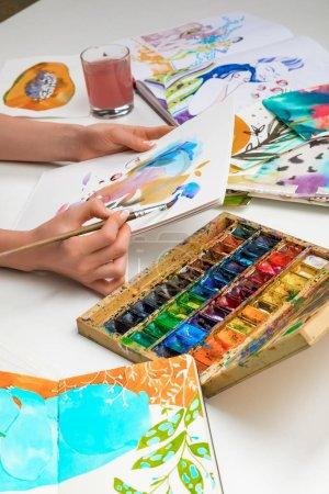 Photo pour Mise au point sélective des mains de femmes peinture peintures aquarelles et pinceau sur l'album blanc - image libre de droit